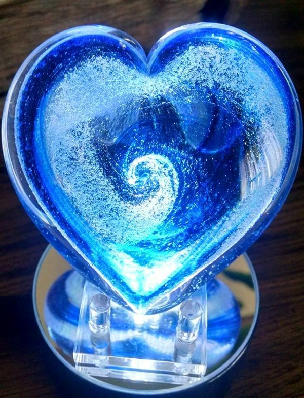 A glowing blue glass heart with ash design inside