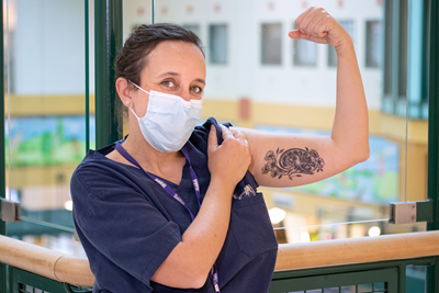 Karen Milford wearing scrubs and a face mask, flexes her arm to reveal an artistic bicep tattoo of a brain and flowers