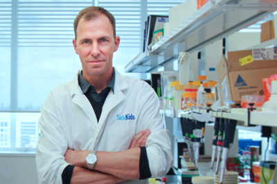 Peter Dirks standing against a laboratory bench, surrounded by lab equipment